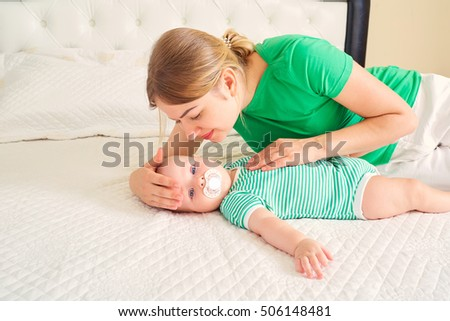 Mom with baby on white bed. mother care for her child. family concept.