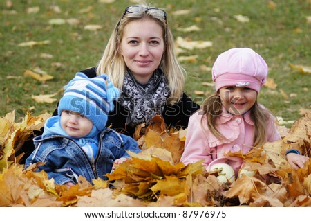 mom with children lying in autumn leaves - stock photo