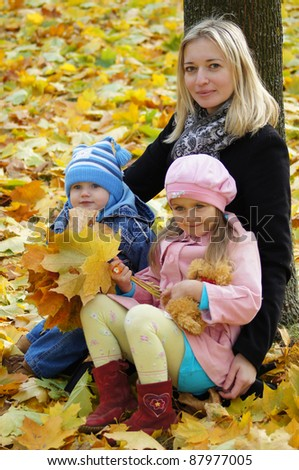 mom with children sitting at autumn leaves - stock photo