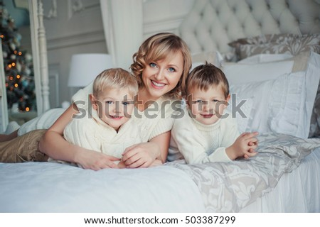 Mom with curly hair and blue eyes, and two sons, blond with blue eyes in a sweater lying on the bed hugging play together at Christmas tree. new Year. Christmas