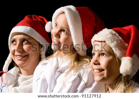 mom with daughter in santa hat on a black background - stock photo