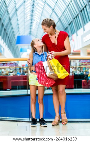 Mom with daughter shopping in mall or store - stock photo