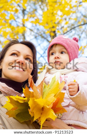 mom with daughter walking at the autumn park