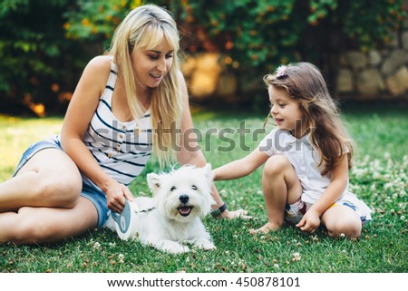Mom with her child relaxing with English Highland White Terrier dog on grass in the backyard - stock photo