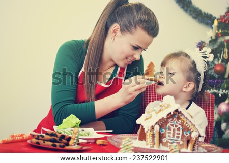 Mom with her daughter prepare ginger house - stock photo