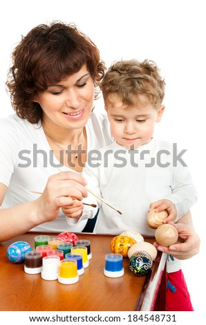 mom with her son decorate Easter eggs on white - stock photo