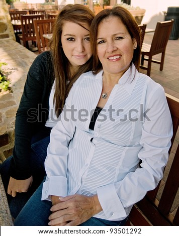 Mom with her teen daughter at an outdoor cafe - stock photo