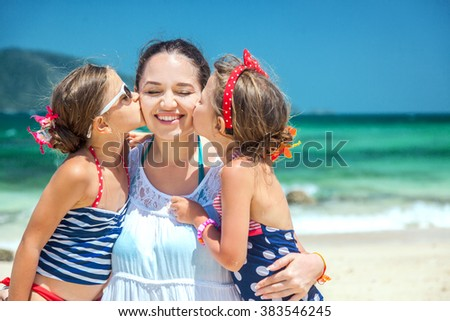 Mom with her two children having fun at the tropical beach, daughters kissing mother - stock photo