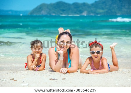 Mom with her two children resting at the tropical beach