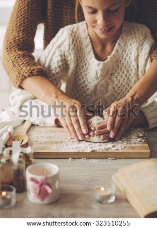 Mom with her 9 years old daughter are cooking holiday pie in the kitchen, lifestyle photo series, hands closeup. - stock photo
