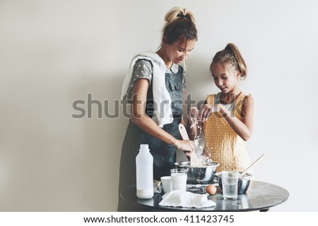 Mom with her 10 years old daughter dressed in linen aprons are cooking together over light wall, lifestyle photo series - stock photo