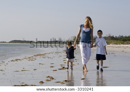 Mom  with kids walking on a beach.  Sky and ocean in the background. - stock photo