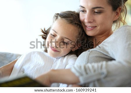 Mom with little girl reading book in sofa - stock photo