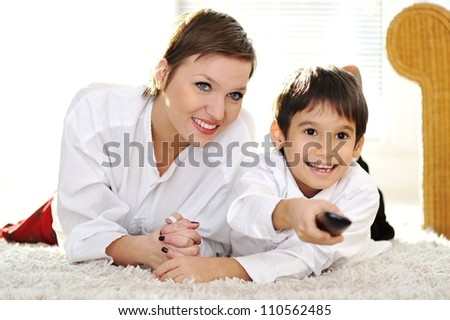Mom with son lying on floor and watching tv using remote control - stock photo