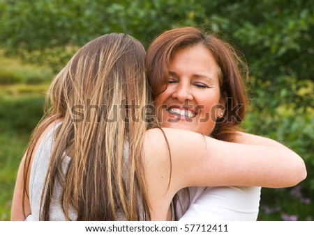 Mom with teen daughter receiving a hug - stock photo