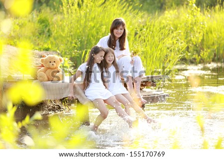 Mom with two daughters on a picnic by the lake splashing and playing