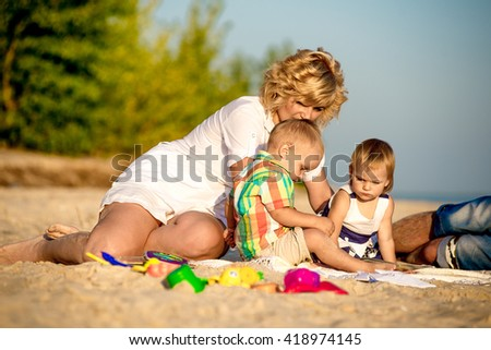 mom with two small children on the beach relaxing in the summer. Family reading a book with children on the beach.
