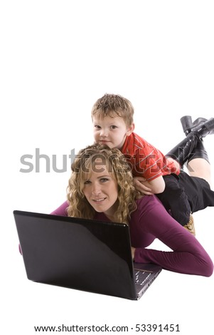 Mom working on a computer with her son on her back - stock photo