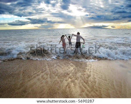 Mom, 3years old and Dad having fun in the waves - stock photo