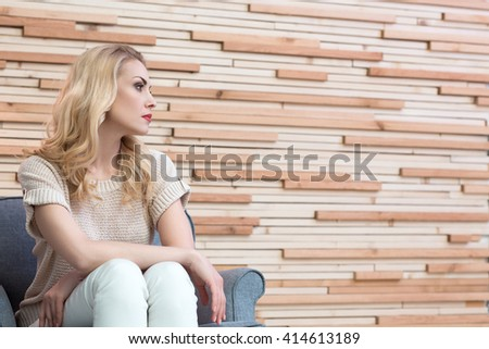 Moment for thinking. Charming adult woman looking away thoughtfully sitting on the armchair - stock photo