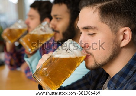 Moment of joy. Closeup shot of a group of male friends enjoying first sips of their beers drinking with their eyes closed - stock photo