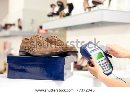 Moment of payment using credit card terminal in shoe store. Selective focus on pair of male shoes on top of box. - stock photo