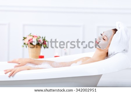 Moment of pleasure. Content nice attractive young woman closing her eyes and feeling glad while taking a bath - stock photo