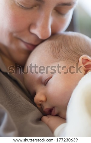 Moments of maternal care and tranquility: Serene baby boy sleeping on mother's chest while she's embracing him with love. - stock photo