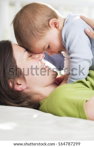 Moments of tenderness: Happy loving mother and baby boy cuddling with affection while lying down in bed. - stock photo