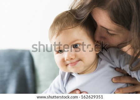 Moments of tenderness: Loving mother embracing and kissing her baby boy. - stock photo