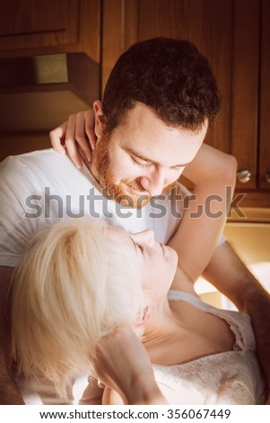Moments of tenderness. Young couple enjoying of togetherness at the morning in the kitchen room.  - stock photo