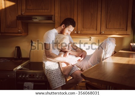 Moments of tenderness. Young couple enjoying of togetherness at the morning in the kitchen room.