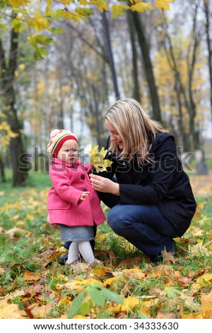 Mommy and little daughter in the autumn park - stock photo
