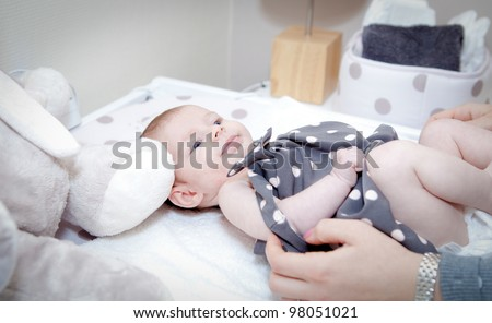 Mommy changing clothes to baby - stock photo