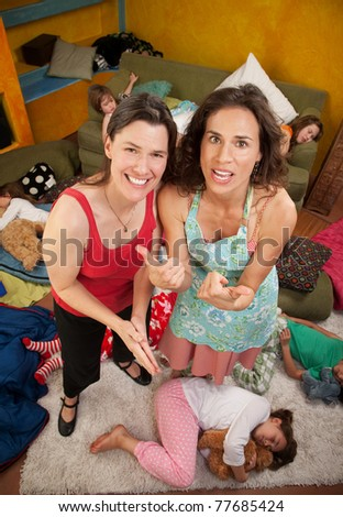 Moms are relieved after little girls fall sleep - stock photo