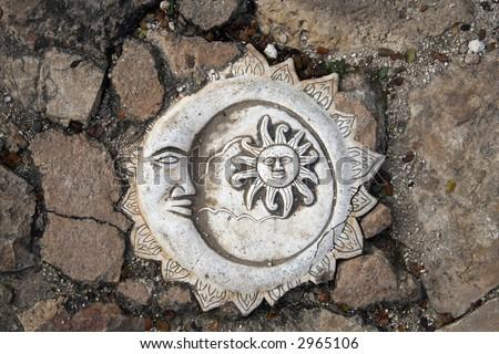 Mon and sun stone sculpture on pavement - stock photo