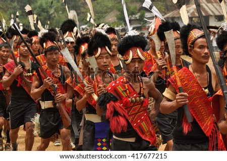Mon, Nagaland - April 2012: Photo of native men in traditional costumes holding rifles and marching during performance at Aoleang festival in Mon, Nagaland. Documentary editorial.