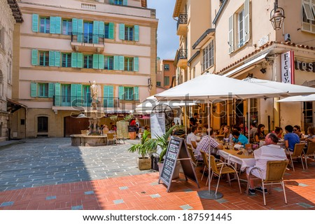 MONACO-VILLE, MONACO - JULY13, 2013: People having dinner in restaurant on small quiet square with fountain surrounded by houses in Monaco-Ville, Monaco  - popular touristic resort and place to visit. - stock photo