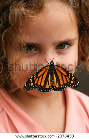 Monarch butterfly on girl's nose - stock photo