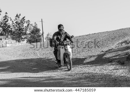 MONASTIRI ODIGITRIAS, CRETE, GREECE - APRIL 21. Monk on scooter in the mountains of south-central Crete near the convent Moni Odigitria on April 21, 2016. Even with the monks, modern life has arrived  - stock photo