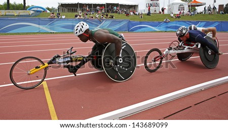MONCTON, CANADA - June 22: Jean-Paul Compaore (left) and Michel Filteau compete in the 10,000-meter run wheelchair event at the Canadian Track & Field Championships June 22, 2013 in Moncton, Canada. - stock photo