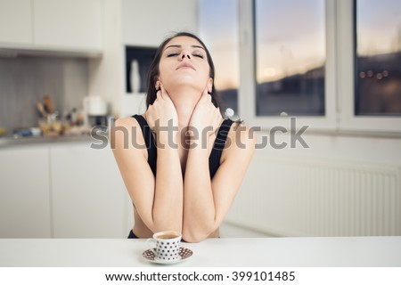 Monday morning.Tired sleepy woman waking up drinking a coffee to wake up early in the morning sunrise.Sore back pain,not enough sleep.Overworked.Insufficient sleep,neck strain.Hangover - stock photo