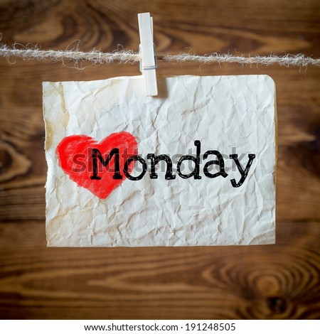 Monday on red heart on aged paper hanging on the clothesline. On old wood background - stock photo