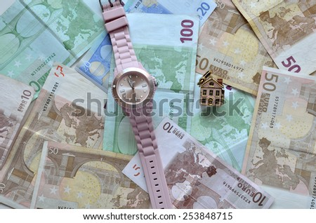 Money, a watch and a small house - stock photo