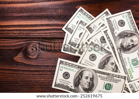 money american hundred dollar bills carelessly scattered on the wooden table - stock photo