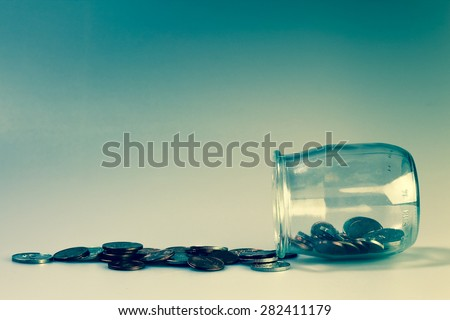 Money and banking concept with coins and jar. - stock photo