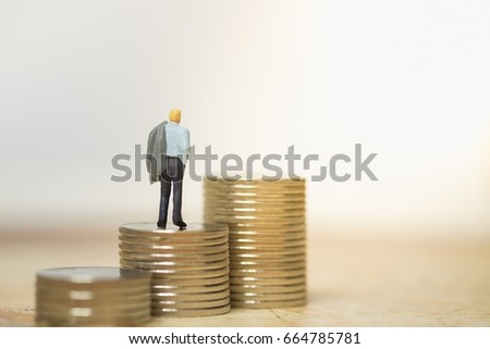 Money and Business Concept. Businessman holding grey jacket on shoulder miniature figure standing, walking and looking on top of stack of coins