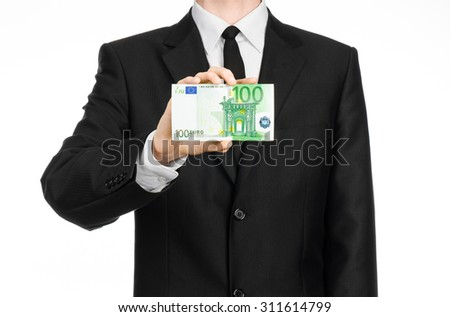 Money and business theme: a man in a black suit holding a bill of 100 euros and shows a hand gesture on an isolated white background in studio - stock photo