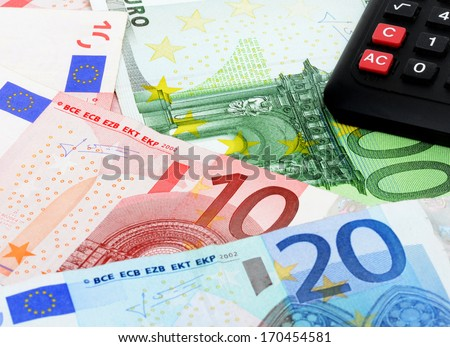 Money and calculator as symbol for exact calculation - stock photo