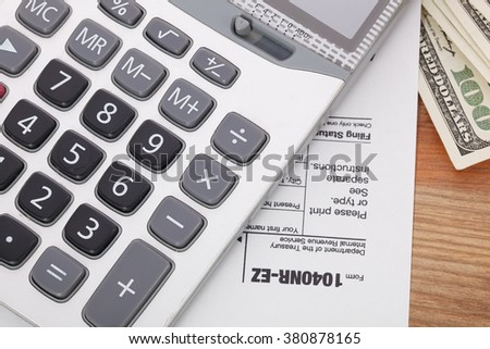 Money and calculator on tax form background